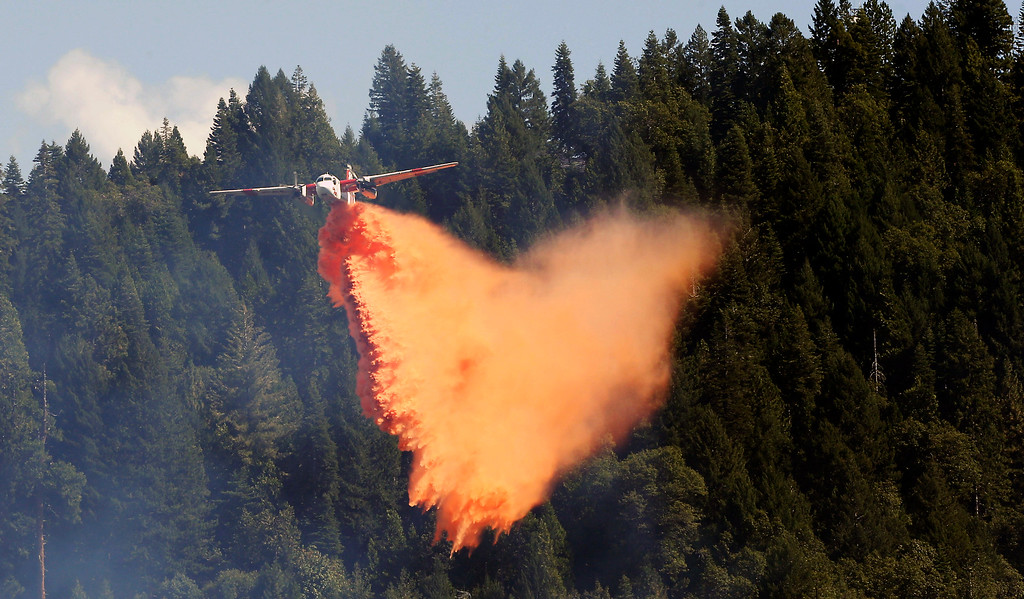 . An aerial tanker drops its load of fire retardant on the fire near Pollack Pines, Calif., Monday, Sept. 15, 2014. The fire, which started Sunday has consumed more than 3,000 acres and forced the evacuation of dozens of homes.(AP Photo/Rich Pedroncelli)