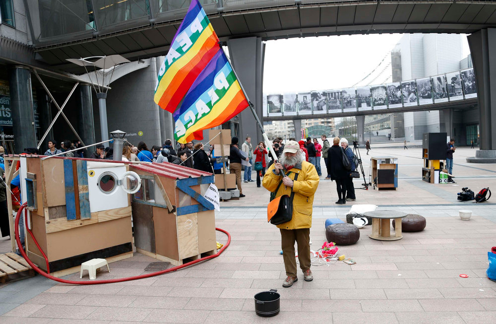 . A man holding a peace flag walks past a mock makeshift house during a protest against Romani evictions in front of the European Union Parliament to mark the International Roma Day in Brussels on April 8, 2013.  REUTERS/Francois Lenoir