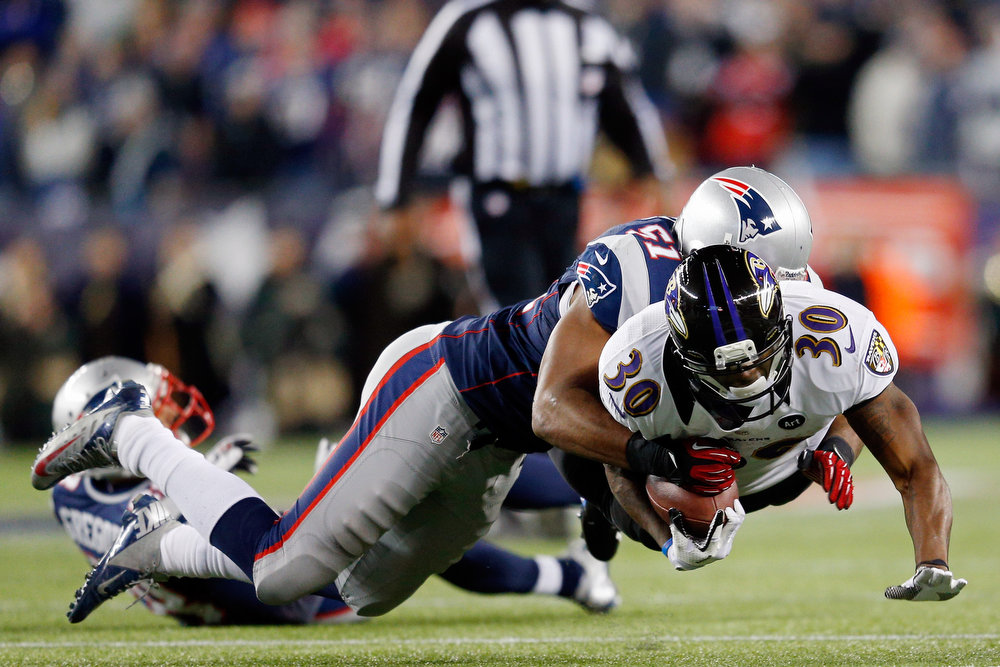 . Bernard Pierce #30 of the Baltimore Ravens gets tackled by Jerod Mayo #51 of the New England Patriots during the 2013 AFC Championship game at Gillette Stadium on January 20, 2013 in Foxboro, Massachusetts.  (Photo by Jim Rogash/Getty Images)