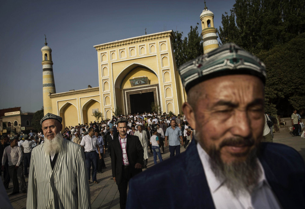 . KASHGAR, CHINA - JULY 29:  Uyghur men leave the Id Kah Mosque following the Eid prayers on July 29, 2014 in old Kashgar, Xinjiang Province, China. Nearly 100 people have been killed in unrest in the restive Xinjiang Province in the last week in what authorities say is terrorism but advocacy groups claim is a result of a government crackdown to silence opposition to its policies. China\'s Muslim Uyghur ethnic group faces cultural and religious restrictions by the Chinese government. Beijing says it is investing heavily in the Xinjiang region but Uyghurs are increasingly dissatisfied with the influx of Han Chinese and uneven economic development.  (Photo by Kevin Frayer/Getty Images)