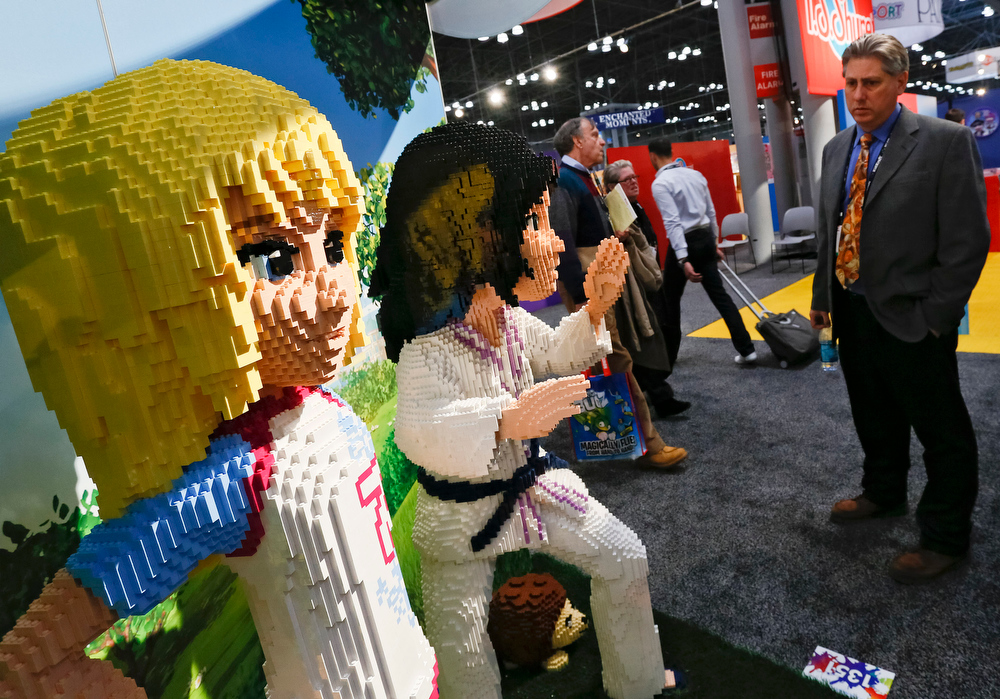 Description of . Attendees of the American International Toy Fair enjoy the work of LEGO Master Builders who created 6-foot tall figures of the Toy of the Year Award-winning LEGO Friends collection of building sets on Sunday, Feb. 10, 2012, in New York. (Brian Ach/AP Images for LEGO Systems, Inc.)