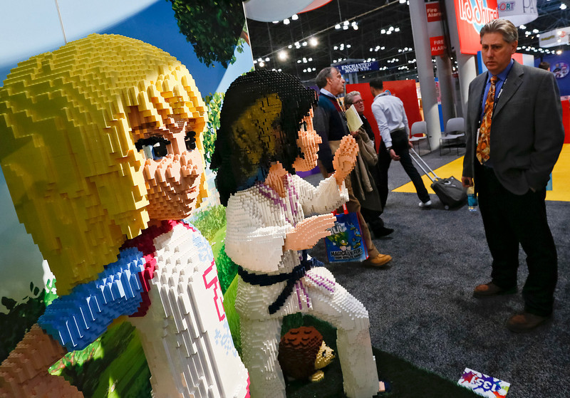 . Attendees of the American International Toy Fair enjoy the work of LEGO Master Builders who created 6-foot tall figures of the Toy of the Year Award-winning LEGO Friends collection of building sets on Sunday, Feb. 10, 2012, in New York. (Brian Ach/AP Images for LEGO Systems, Inc.)