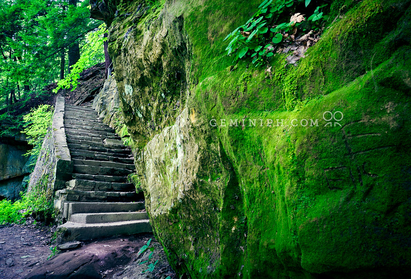Stone steps wrapping around a moss-covered rock wall.