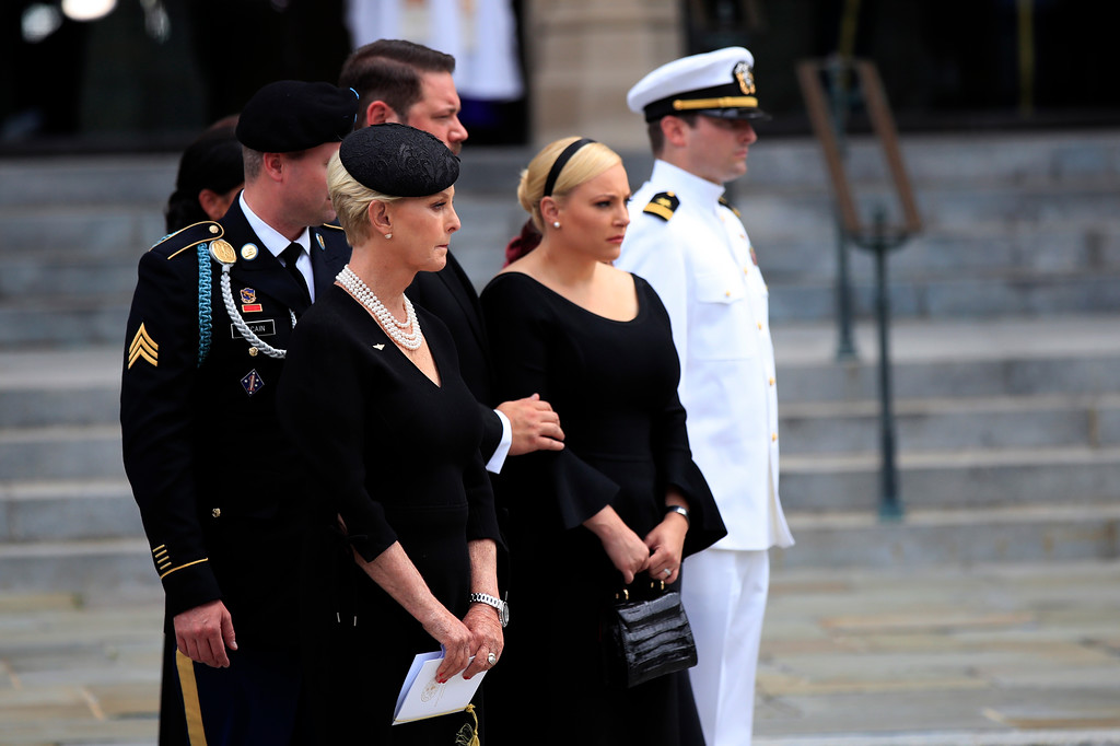 . The family of Sen. John McCain, R-Ariz., from left, Jimmy McCain, Cindy McCain, Ben Domenech and his wife Meghan McCain, and Jack McCain watch as the casket is placed into the hearse following a memorial service at the Washington National Cathedral in Washington, Saturday, Sept. 1, 2018. (AP Photo/Manuel Balce Ceneta)