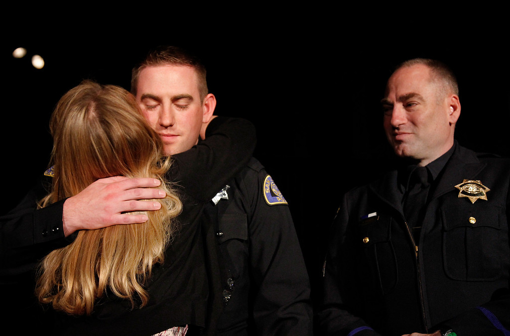 . At center, San Jose Police Department Recruit Officer Chad Barrett hugs his mom Tracy Barrett as his father Bill Barrett, right looks on at the San Jose Police Academy graduation in San Jose, Calif. on Friday, March 15, 2013.   (LiPo Ching/Staff)
