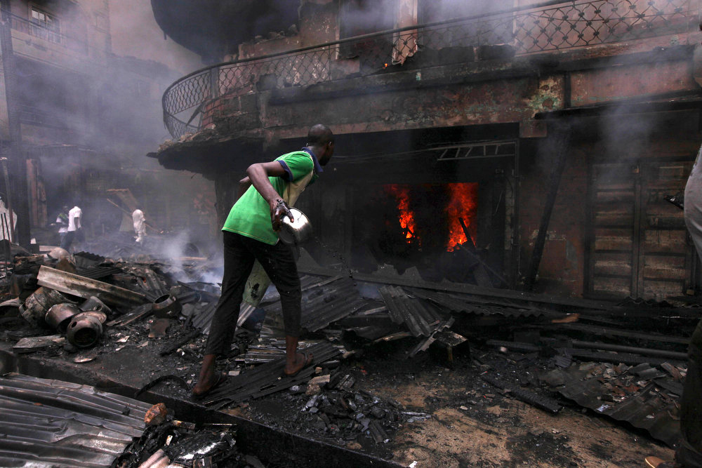 Description of . A man try to contain a fire at  residential homes and a warehouse on Lagos Island in Lagos, Nigeria, Wednesday, Dec. 26, 2012. An explosion ripped through a warehouse Wednesday where witnesses say fireworks were stored in Nigeria\'s largest city, sparking a fire. It wasn\'t immediately clear if anyone was injured in the blast that firefighters and locals struggled to contain. (AP Photos/Sunday Alamba)
