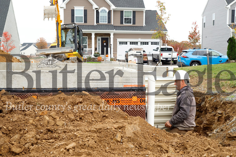 Construction crews from Fischer's Excavating work on a window well egress and French drain at a property in the Weatherburn Heights neighborhood in Mars Friday. Seb Foltz/Butler Eagle 10/25/19