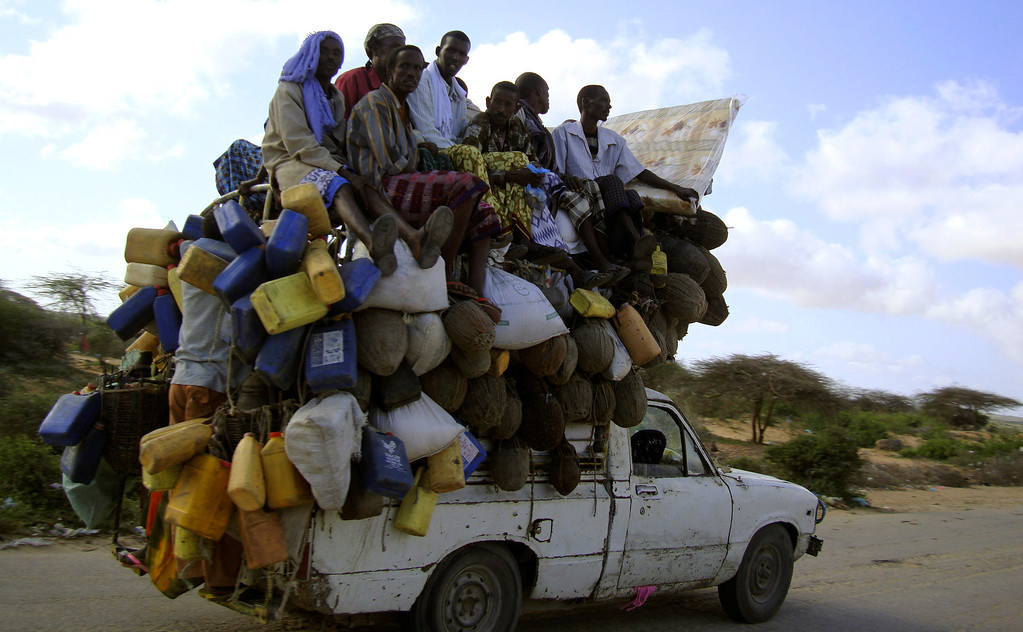 . Residents ride on a pick-up truck that supplies milk and other items in Somalia\'s capital Mogadishu, September 2, 2009. REUTERS/Omar Faruk
