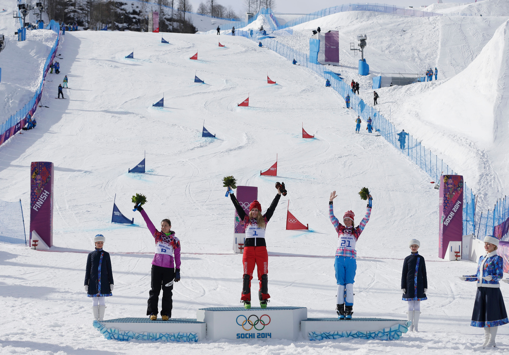 . Women\'s snowboard parallel giant slalom gold medalist Switzerland\'s Patrizia Kummer, center, celebrates on the podium with silver medalist Tomoka Takeuchi of Japan, left, and bronze medalist Alena Zavarzina of Russia at the Rosa Khutor Extreme Park, at the 2014 Winter Olympics, Wednesday, Feb. 19, 2014, in Krasnaya Polyana, Russia. (AP Photo/Andy Wong)