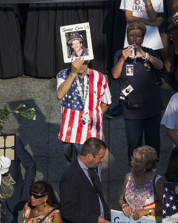 . A man holds up a picture of a firefighter during memorial ceremonies for the twelfth anniversary of the terrorist attacks on lower Manhattan at the World Trade Center site on September 11, 2013 in New York City.  (Photo by Andrew Burton/Getty Images)