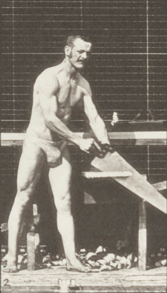 Man in pelvis cloth sawing a board