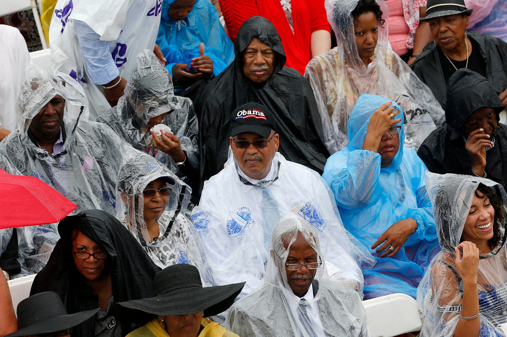 . Audience members sit in rain for the 50th Anniversary of the March on Washington, Wednesday, Aug. 28, 2013, in front of the Lincoln Memorial in Washington, where Martin Luther King, Jr. spoke. President Barack Obama is scheduled to speak later in the day.   (AP Photo/Charles Dharapak)