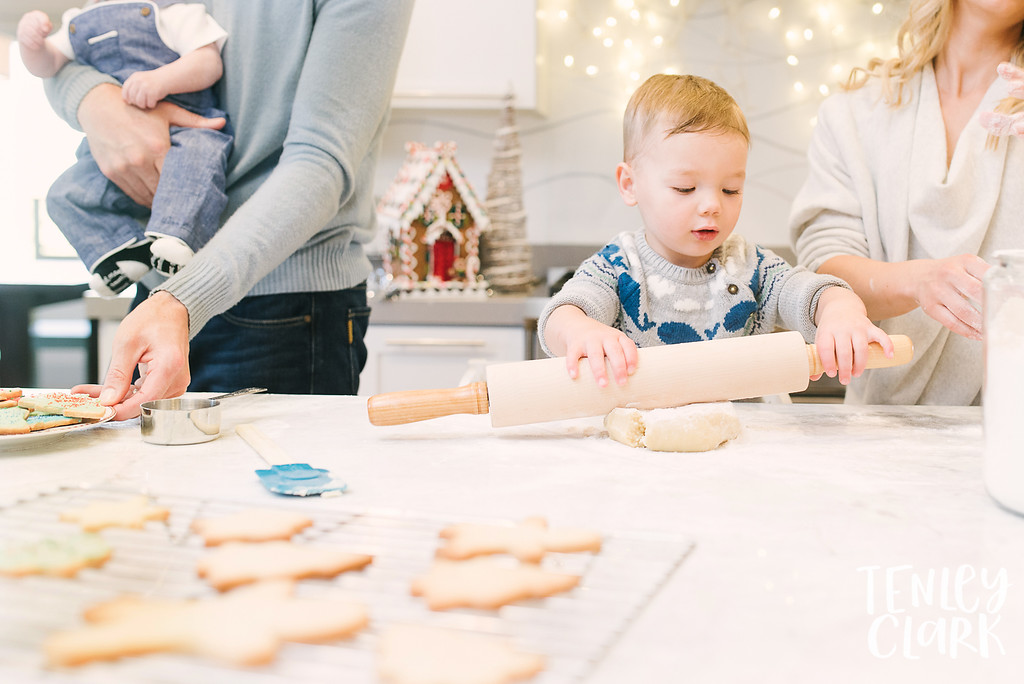 Lifestyle in home family photography session of family baking Christmas cookies and wearing holiday pajamas by Tenley Clark Photography.