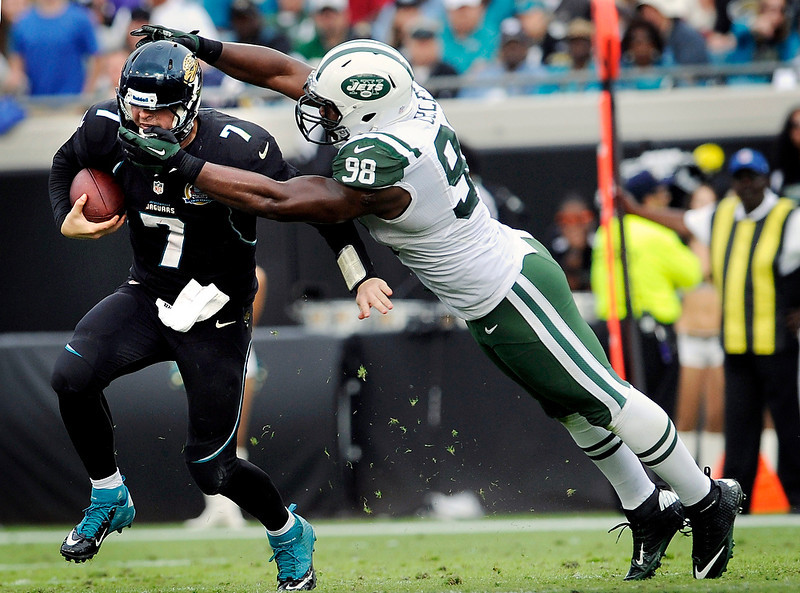 . Jacksonville Jaguars quarterback Chad Henne (7) is tackled by the face mask by New York Jets defensive end Quinton Coples (98) during the second half of an NFL football game, Sunday, Dec. 9, 2012, in Jacksonville, Fla. The Jets won 17-10. (AP Photo/Stephen Morton)