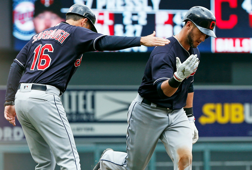 . Cleveland Indians\' Yan Gomes,, right, is congratulated by third base coach Mike Sarbaugh as he rounds the bases with a three-run home run off Minnesota Twins relief pitcher Ryan Pressly in the eighth inning of the first baseball game of a doubleheader, Thursday, Aug. 17, 2017, in Minneapolis. The Indians won 9-3. (AP Photo/Jim Mone)