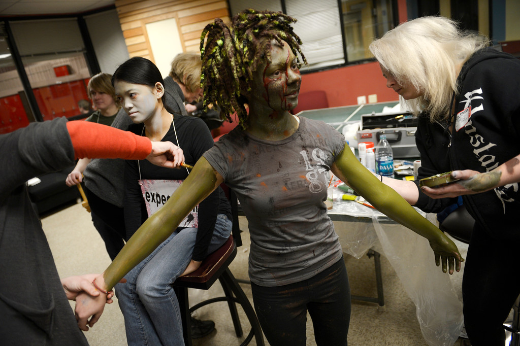 """. BOULDER, CO- FEBRUARY 19:   Kristy Pike, left, and Danica Minor, right, both  make-up artists with Theatrical Costumes Etc., apply \""""Zombie\"""" make up to zombie Sydney McVicker, 14.   With the help of a professional videographer, Fairview High School students produced a zombie video to advertise an Awareness Drive in Boulder Valley schools designed to bring attention to a variety of mental health and wellness issues.  Students were made to look like zombies by make-up artists from Theatrical Costumes, Etc. (Photo By Helen H. Richardson/ The Denver Post)"""
