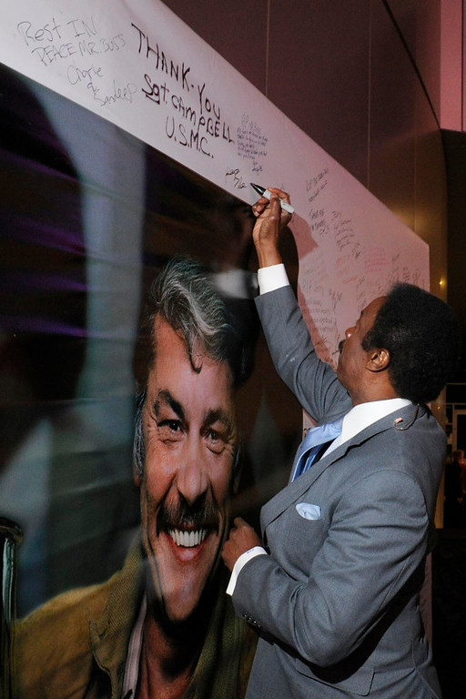 . Los Angeles Sports Caster Jim Hill signs a poster. The Lakers posted large banners around LA Live and Staples Center with a photo of Jerry Buss and plenty of room for fans to write their best wishes. Los Angeles, CA 2/20/2013(John McCoy/Staff Photographer)