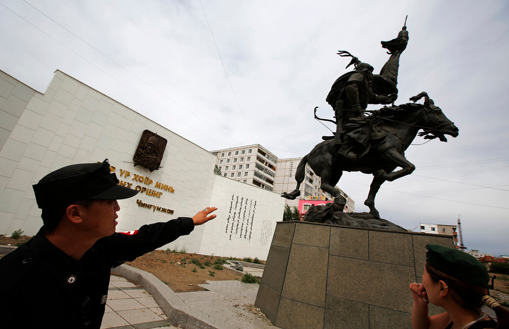 . Ariunbold (L) and Uranjargal, leaders of the Mongolian neo-Nazi group Tsagaan Khass, stand next to a statue of Chingunjav, a Mongolian national hero, in Ulan Bator June 22, 2013. The group has rebranded itself as an environmentalist organisation fighting pollution by foreign-owned mines, seeking legitimacy as it sends Swastika-wearing members to check mining permits. Over the past years, ultra-nationalist groups have expanded in the country and among those garnering attention is Tsagaan Khass, which has recently shifted its focus from activities such as attacks on women it accuses of consorting with foreign men to environmental issues, with the stated goal of protecting Mongolia from foreign mining interests. This ultra-nationalist group was founded in the 1990s and currently has 100-plus members. Picture taken June 22, 2013. REUTERS/Carlos Barria