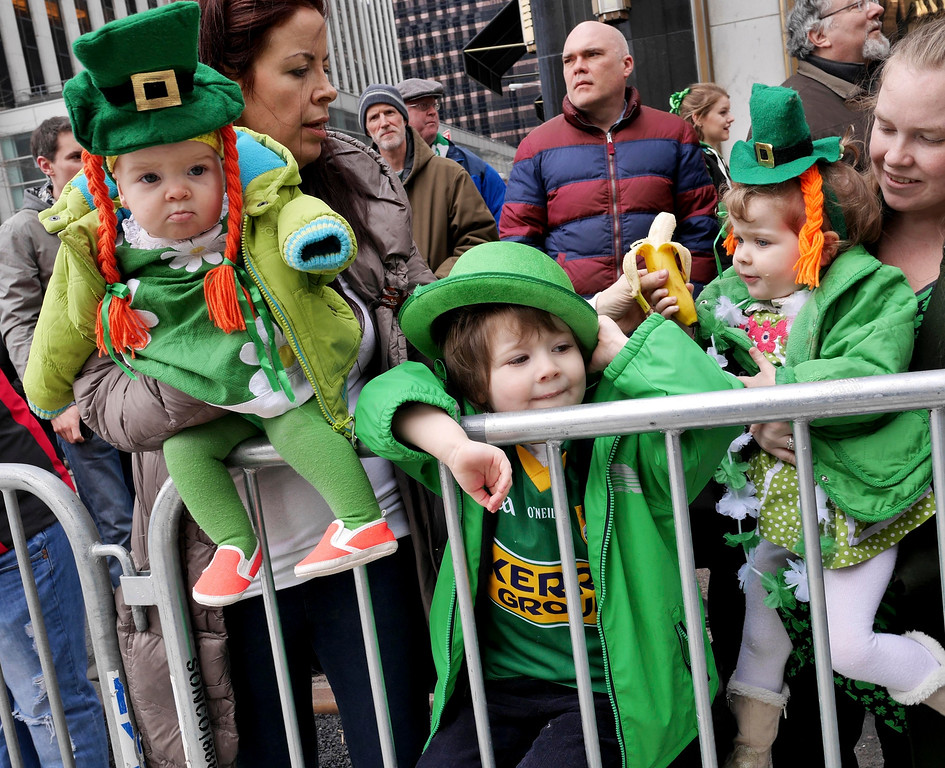. Auston O\'Grady, 3, center, and his sisters Billie O\'Grady, 7 months, right, and Zola O\'Grady, 2, watch the St. Patrick\'s Day Parade in New York, Tuesday, March 17, 2015. (AP Photo/Seth Wenig)