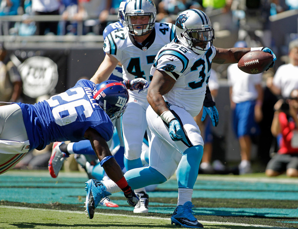 . Carolina Panthers fullback Mike Tolbert (35) runs past New York Giants strong safety Antrel Rolle (26) for a touchdown during the first half of an NFL football game in Charlotte, N.C., Sunday, Sept. 22, 2013. (AP Photo/Bob Leverone)