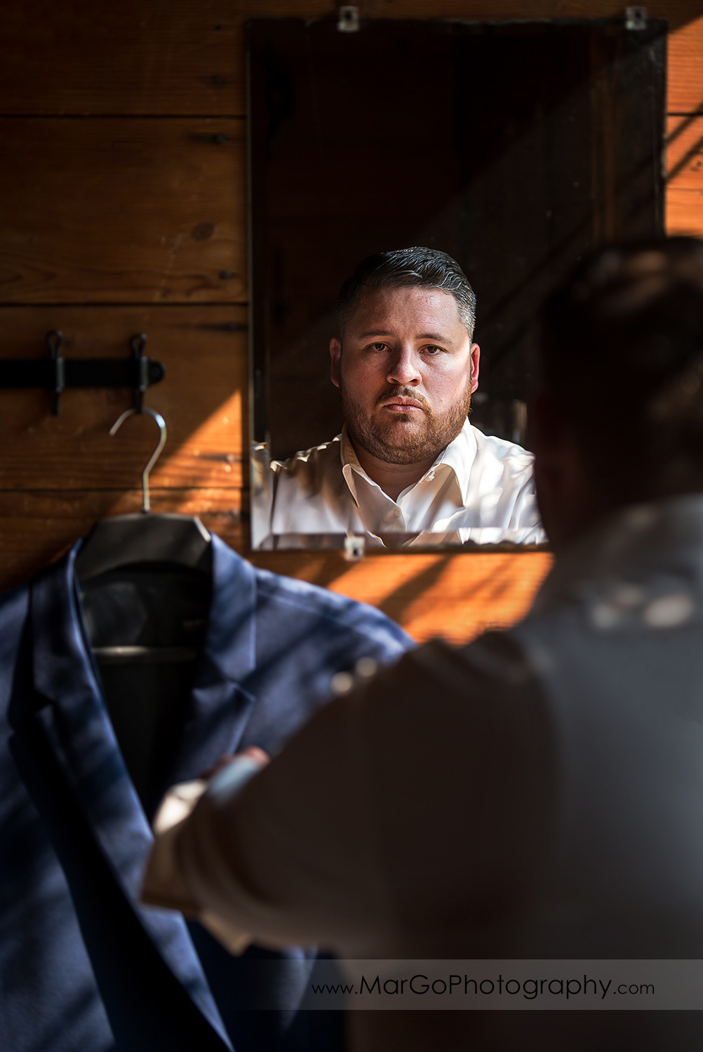groom getting ready in front of mirror at Taber Ranch Vineyards