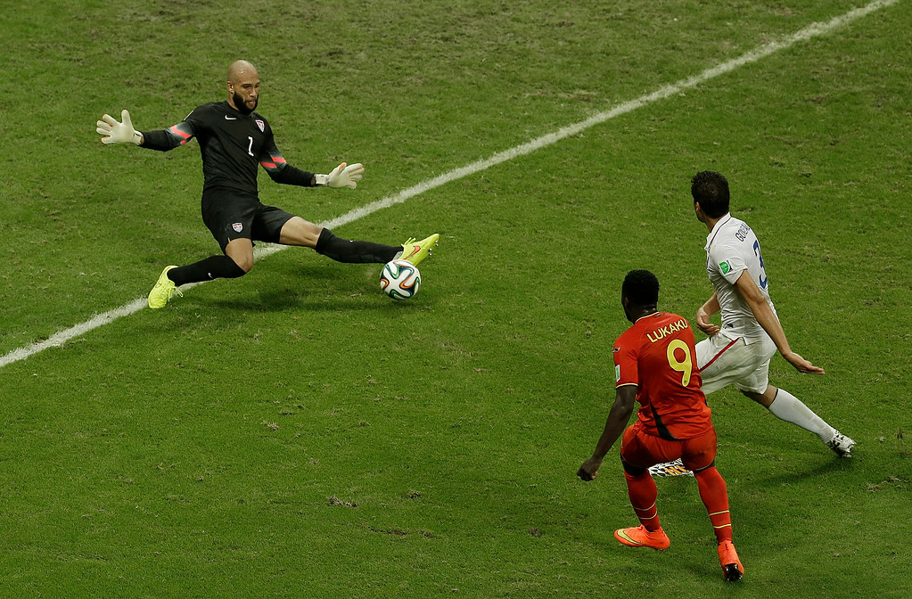 . United States\' goalkeeper Tim Howard, left, makes a save as Belgium\'s Romelu Lukaku, front, looks on during the World Cup round of 16 soccer match between Belgium and the USA at the Arena Fonte Nova in Salvador, Brazil, Tuesday, July 1, 2014. (AP Photo/Themba Hadebe)