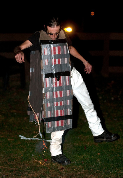 John Fletcher of Pinckney, 50, aka Ghengis John the Human Firecracker, lets go of an ultra fast wick that will set off 6000 firecrackers strapped to a leather vest outside Burroughs Tavern in Brighton, MI on Oct 26, 2012.  (Mark Bialek / Special to the Det News)