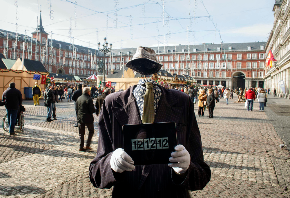 Description of . A street performer poses with an iPad with the time reading 12:12:12 in the Plaza Mayor in Madrid, December 12, 2012.  December 12, 2012 is the last day in this century where the numeral date can be all the same number. REUTERS/Paul Hanna