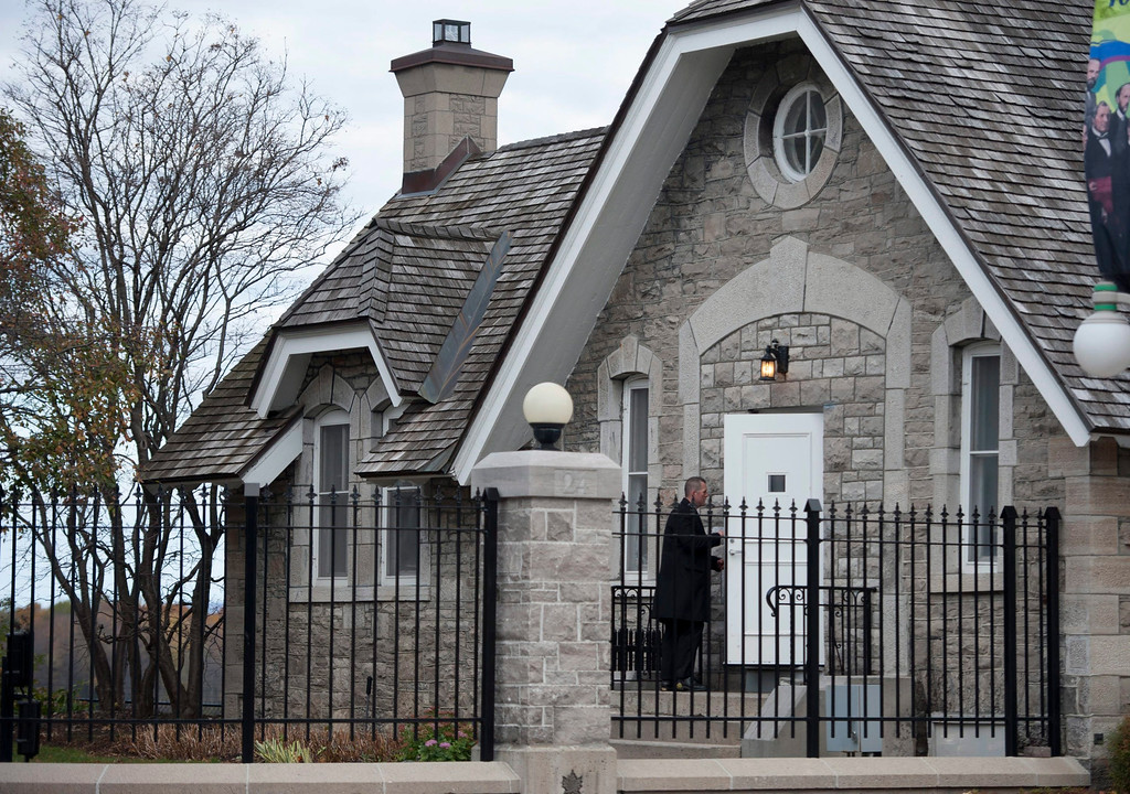 . A heavily armed RCMP officer enters 24 Sussex Dr., the official residence of the Prime Minister, on Wednesday, Oct. 22, 2014.  A soldier standing guard at the National War Memorial has been shot by an unknown gunman and there have been reports of gunfire inside the halls of Parliament. (AP Photo/The Canadian Press, Justin Tang)