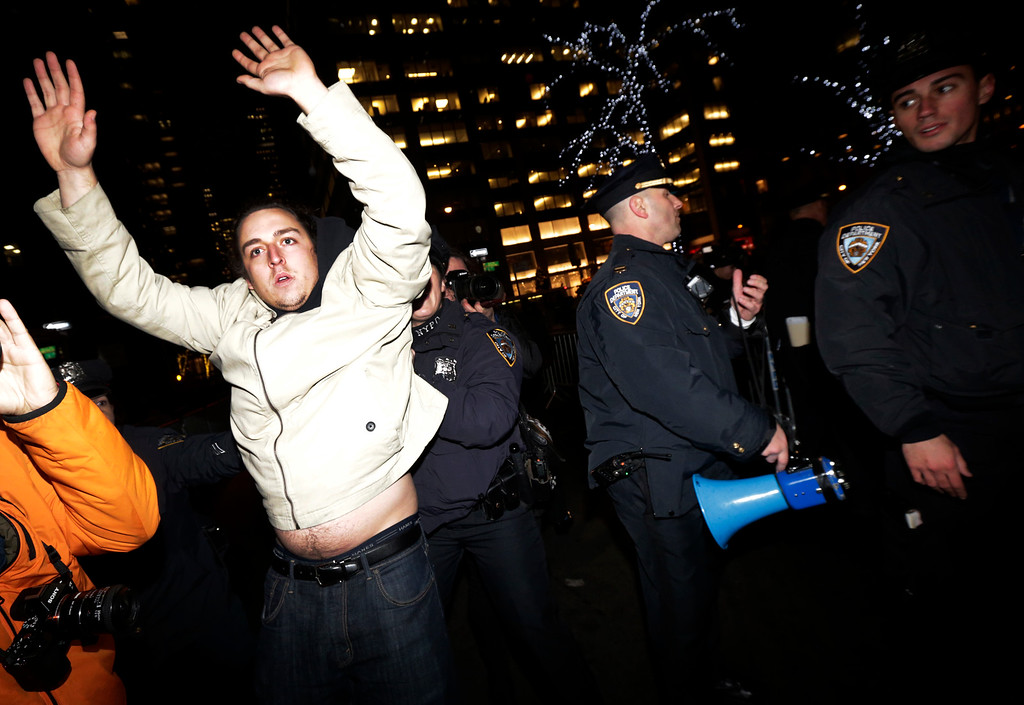 . A man, left, holds his hands up as New York City Police officers secure a street near Rockefeller Center during a protest after it was announced that the police officer involved in the death of Eric Garner is not being indicted, Wednesday, Dec. 3, 2014, in New York. A grand jury cleared the white New York City police officer Wednesday in the videotaped chokehold death of Garner, an unarmed black man, who had been stopped on suspicion of selling loose, untaxed cigarettes, a lawyer for the victim\'s family said. A video shot by an onlooker and widely viewed on the Internet showed the 43-year-old Garner telling a group of police officers to leave him alone as they tried to arrest him. The city medical examiner ruled Garner\'s death a homicide and found that a chokehold contributed to it. (AP Photo/Julio Cortez)