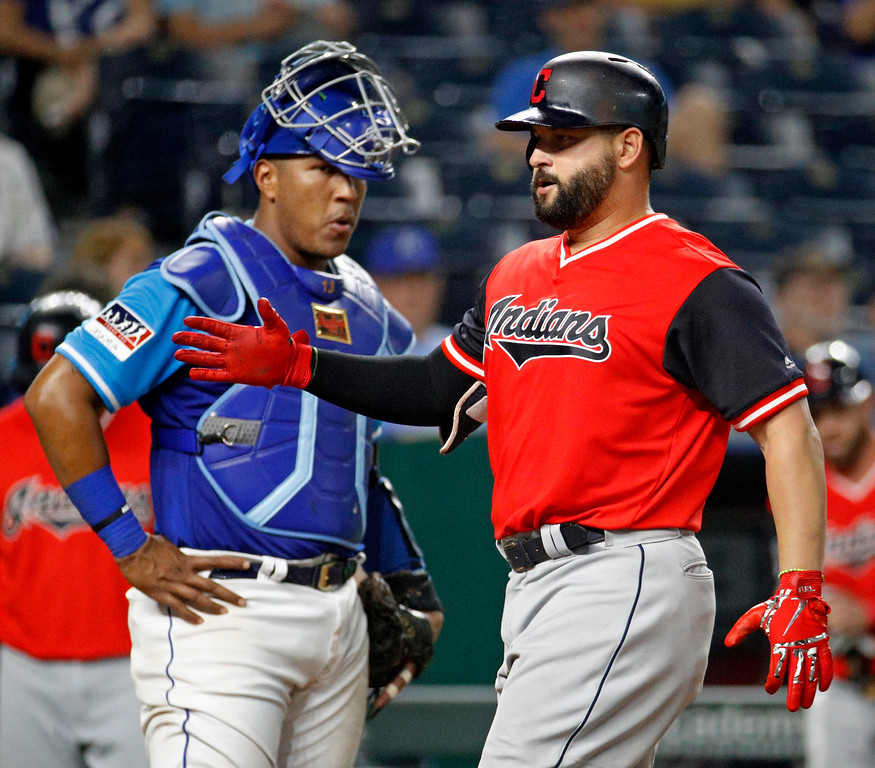 . Cleveland Indians\' Yonder Alonso crosses the plate past Kansas City Royals catcher Salvador Perez after hitting a two-run home run during the eighth inning of a baseball game Friday, Aug. 24, 2018, in Kansas City, Mo. (AP Photo/Charlie Riedel)