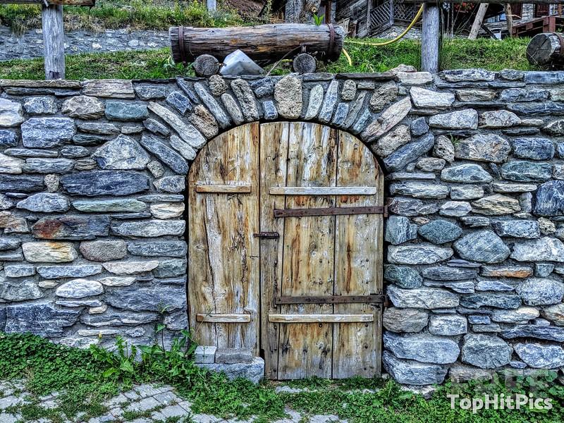 A Wooden Door In A Stone Wall in Vetan, Aosta Valley, Italy