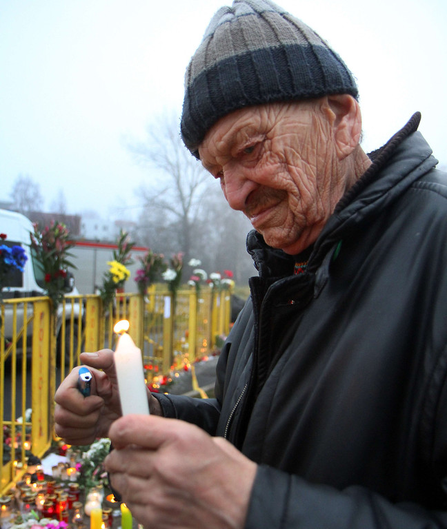 . A man lights a candle near a barricade surrounding the Maxima supermarket in Riga on November 23, 2013, after the roof of the building caved in on shoppers on November 21.   AFP PHOTO / PETRAS  MALUKAS/AFP/Getty Images