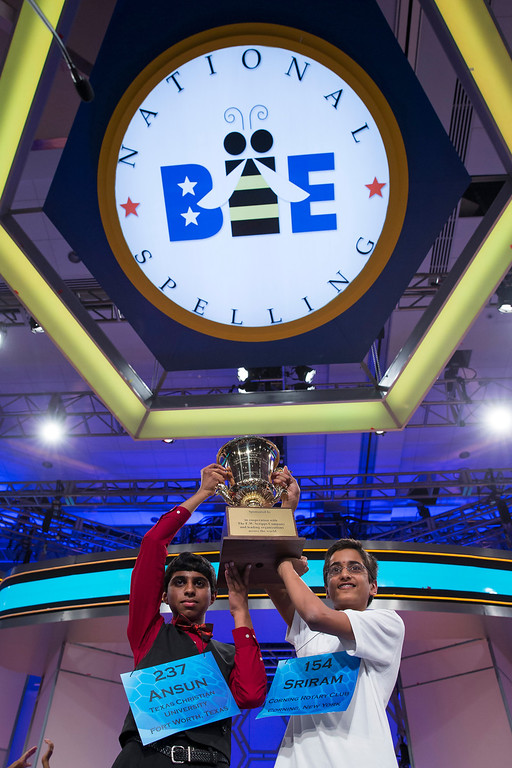 . Ansun Sujoe, 13, of Fort Worth, Texas, left, and Sriram Hathwar, 14, of Painted Post, N.Y., raise the championship trophy after being named co-champions of the National Spelling Bee, on Thursday, May 29, 2014, in Oxon Hill, Md. (AP Photo/ Evan Vucci)