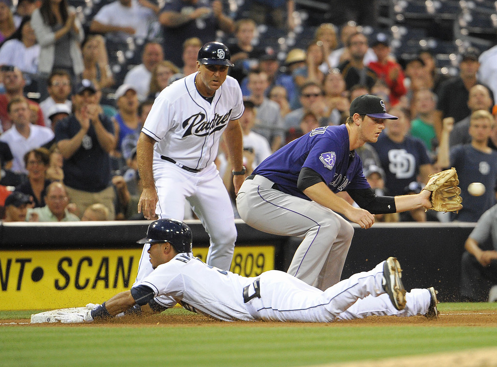 . Alexi Amarista #5 of the San Diego Padres slides into third base with a triple ahead of the throw to DJ LeMahieu #9 of the Colorado Rockies during the third inning of a baseball game at Petco Park on July 9, 2013 in San Diego, California.  (Photo by Denis Poroy/Getty Images)