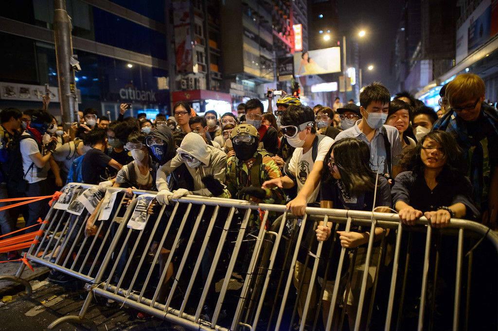 . Pro-democracy protesters remove barriers before clashing with police on a road in the Mong Kok district of Hong Kong early on October 19, 2014. AFP PHOTO / Ed JonesED JONES/AFP/Getty Images