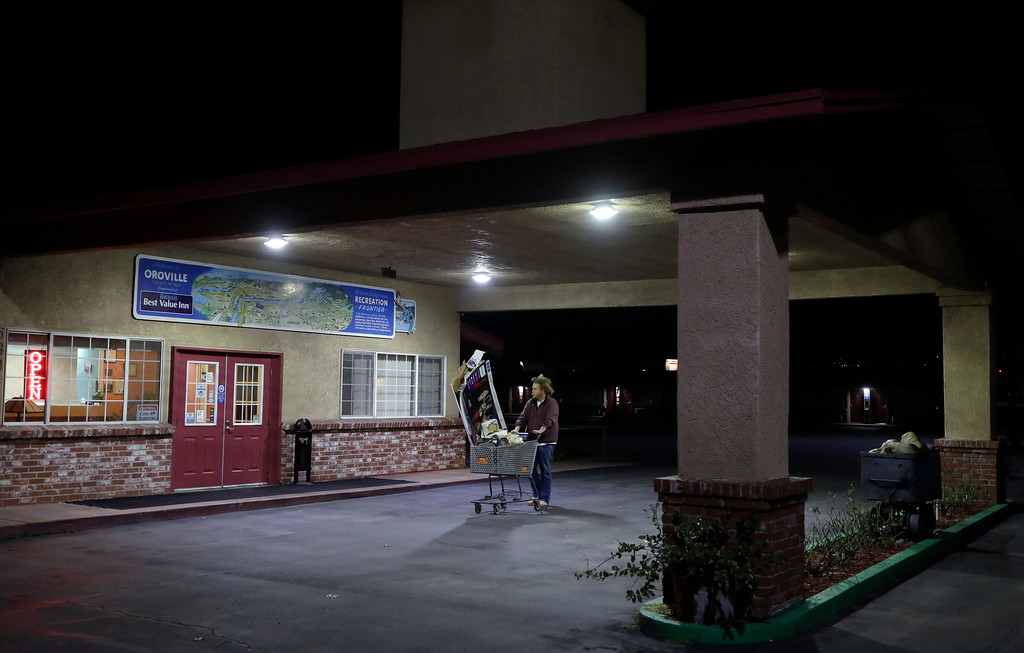 . A man walks past an empty hotel, with the sign left on, after an evacuation order under threat from spillage from the Oroville Dam in Oroville, Calif., Monday, Feb. 13, 2017. Helicopters dropped giant rock-filled sandbags into place Monday to shore up the California reservoir that had threatened to breach its banks and unleash a 30-foot wall of water, but officials said the evacuation order would stay in place until they are sure it\'s safe to return home. (AP Photo/Marcio Jose Sanchez)