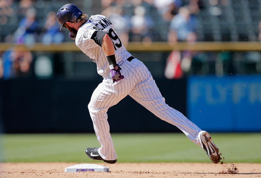 . DENVER, CO - SEPTEMBER 17:  Charlie Blackmon #19 of the Colorado Rockies rounds second base as he scores on a triple by Josh Rutledge #14 of the Colorado Rockies to give the Rockies a 13-0 lead over the Los Angeles Dodgers in the fifth inning at Coors Field on September 17, 2014 in Denver, Colorado. The Rockies defeated the Dodgers 16-2.  (Photo by Doug Pensinger/Getty Images)