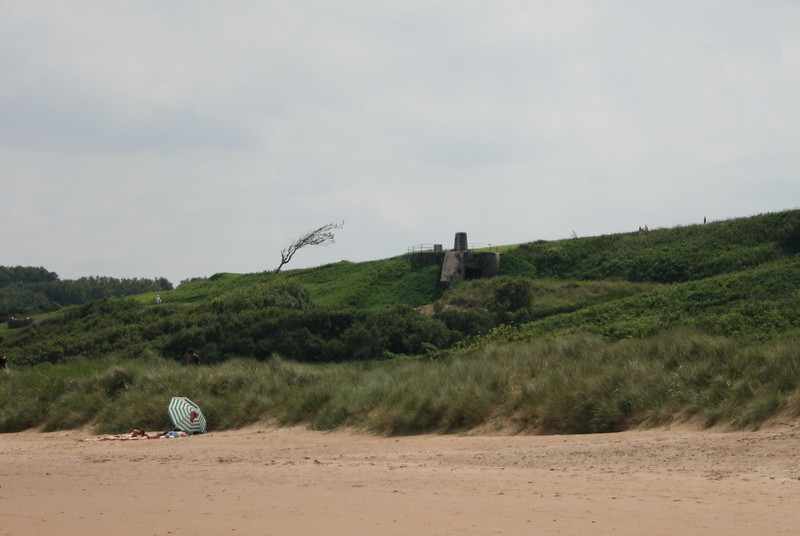 Today beach umbrellas co-exist side by side with the remains of cement bunkers.