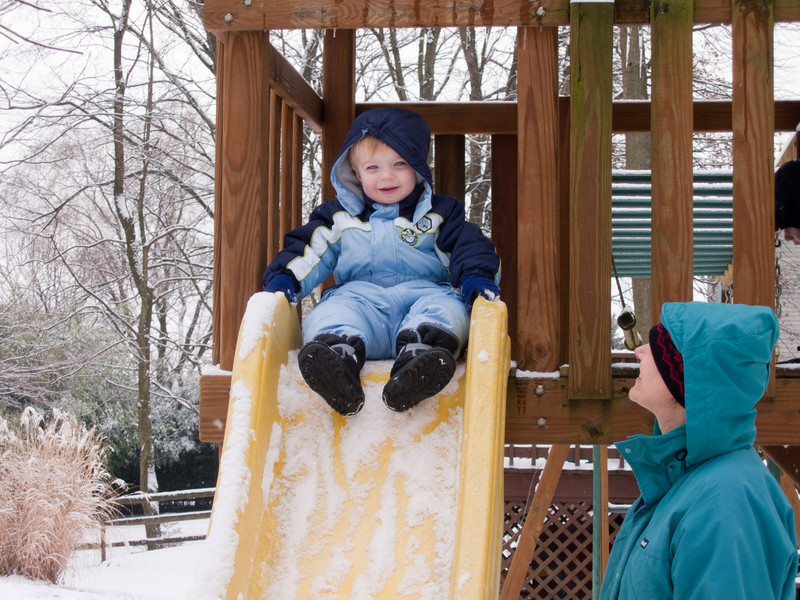 Ethan is ready for a ride down the slide as Laura looks on.