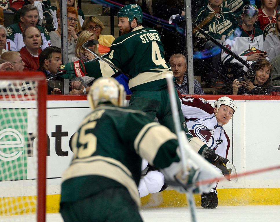 . Colorado Avalanche left wing Cody McLeod (55) gets hit up against the boards by Minnesota Wild defenseman Clayton Stoner (4) during the second period April 21, 2014 during round 1 game three of the Stanley Cup Playoffs at Xcel Energy Center. (Photo by John Leyba/The Denver Post)