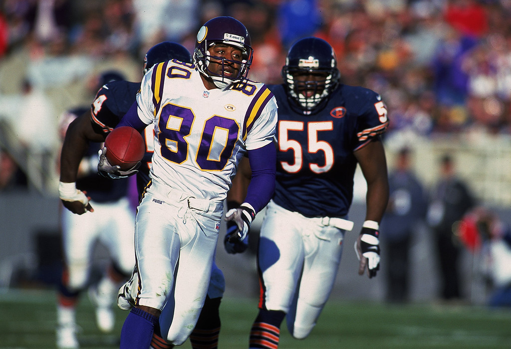 . 14 Nov 1999: Cris Carter #80 of the Minnesota Vikings carries the ball as he is chased by Sean Harris #55 of the Chicago Bears at the Soldier Field in Chicago, Illinois. The Vikings defeated the Bears 27-24 in overtime. Mandatory Credit: Jonathan Daniel  /Allsport