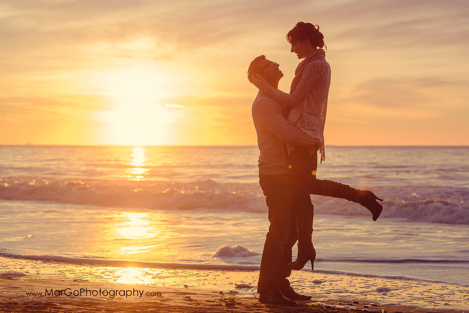 full body sunset photo of man lifting woman in grey sweater and jeans with ocean in background during engagement session at San Francisco Baker Beach