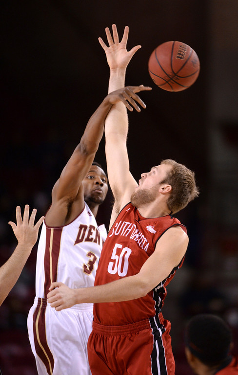 . DENVER, CO. - FEBRUARY 8, 2014: Denver senior forward Chris Udofia (34) punched the ball past South Dakota center Trevor Gruis (50) on the opening tip-off. The University of Denver hosted South Dakota Saturday afternoon, February 8, 2014. Photo By Karl Gehring/The Denver Post