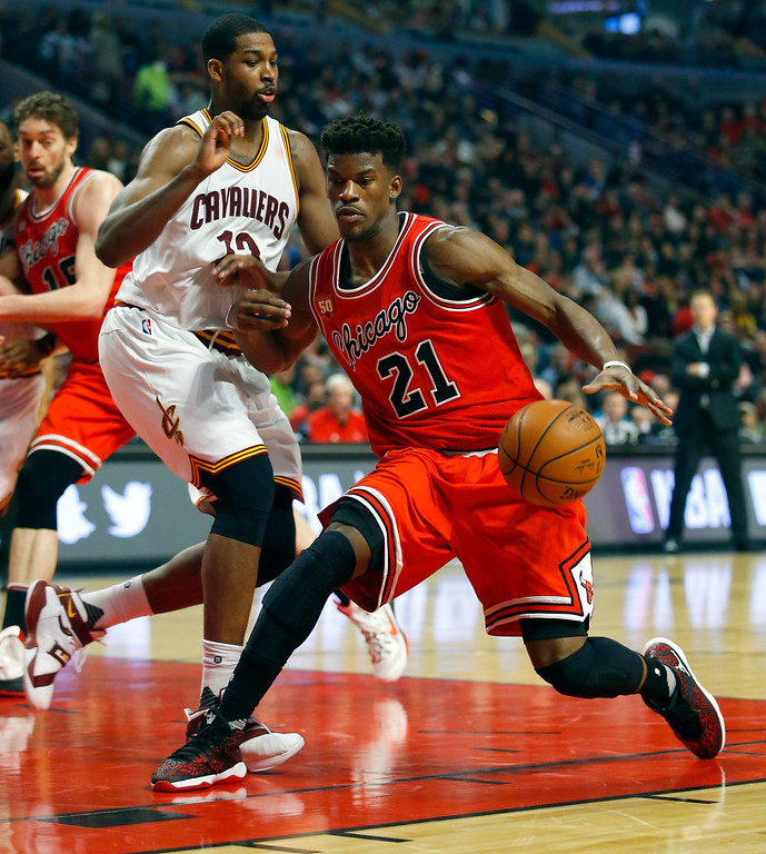 . Chicago Bulls guard Jimmy Butler (21) is guarded by Cleveland Cavaliers center Tristan Thompson (13) during the second half of an NBA basketball game in Chicago on Saturday, April 9, 2016. (AP Photo/Jeff Haynes)