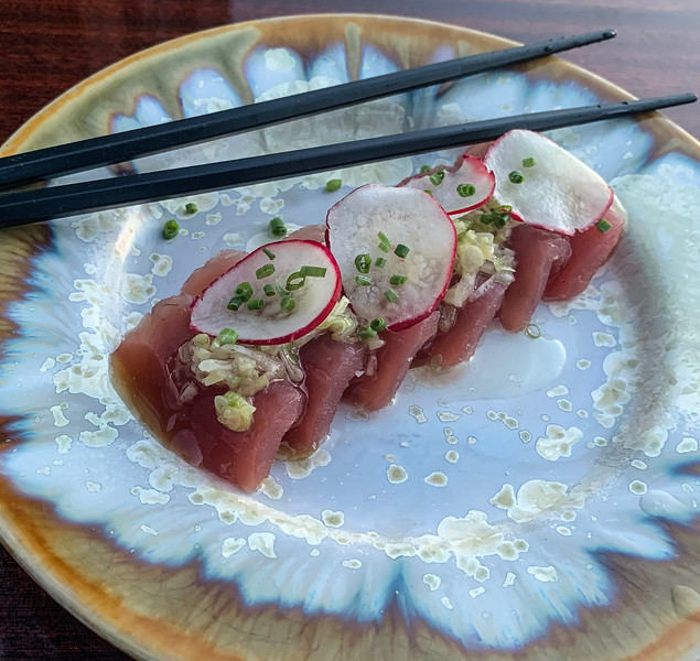 Plate of raw tuna with radishes on top