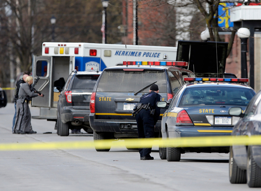 . Law enforcement officers take cover along Main Street in Herkimer, N.Y., when shots were fired while they were searching for a suspect in two shootings that killed four and injured at least two on, Wednesday, March 13, 2013.   (AP Photo/Mike Groll)