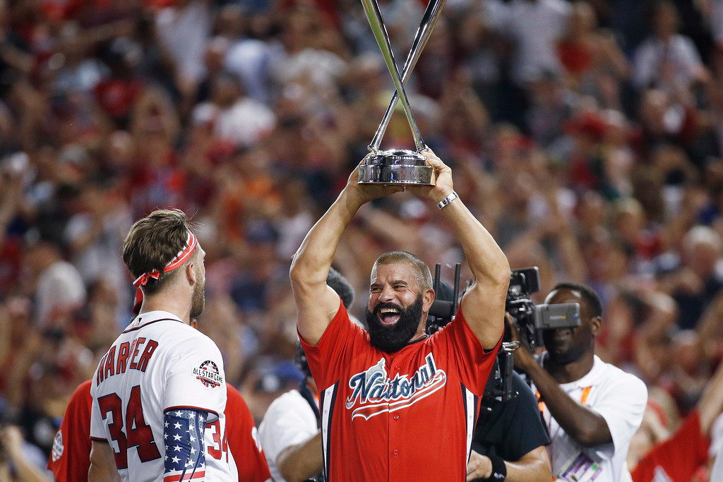. Ron Harper holds his son Washington Nationals Bryce Harper\'s trophy after the Major League Baseball Home Run Derby Monday, July 16, 2018, in Washington. (AP Photo/Patrick Semansky)