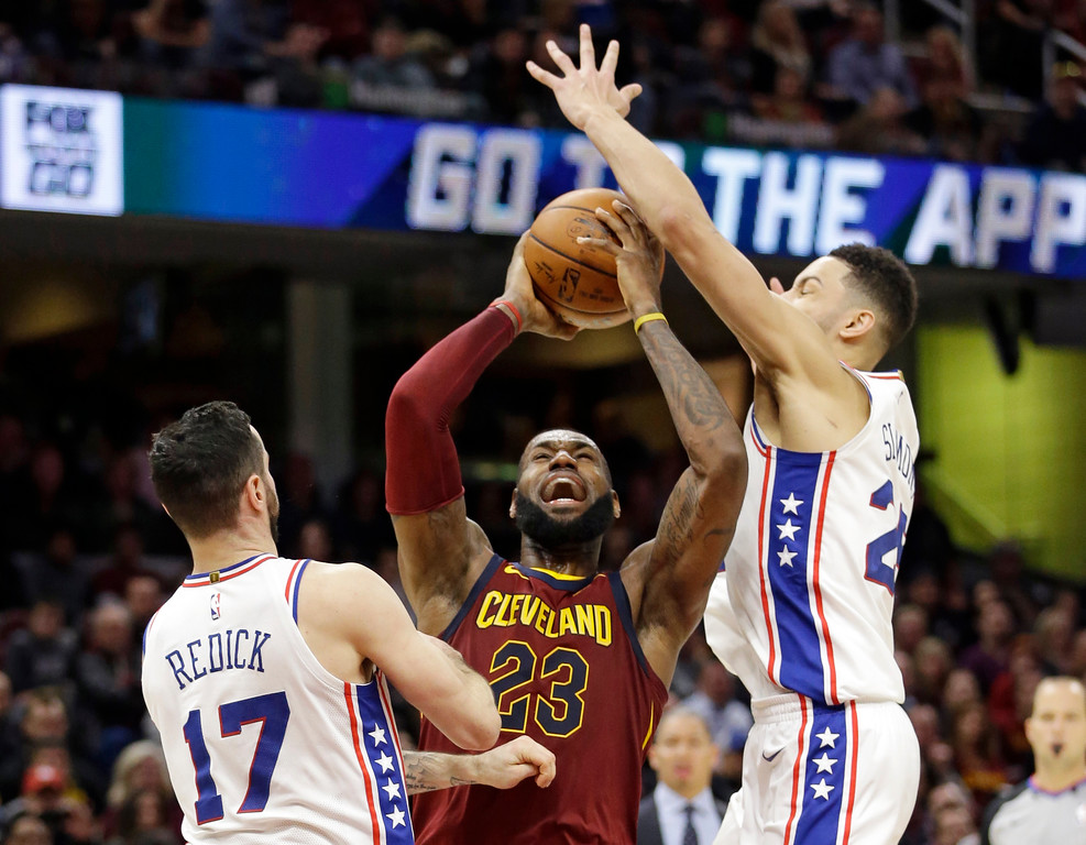 . Cleveland Cavaliers\' LeBron James, center, shoots between Philadelphia 76ers\' JJ Redick, left and Ben Simmons during the second half of an NBA basketball game Saturday, Dec. 9, 2017, in Cleveland. The Cavaliers won 105-98. (AP Photo/Tony Dejak)