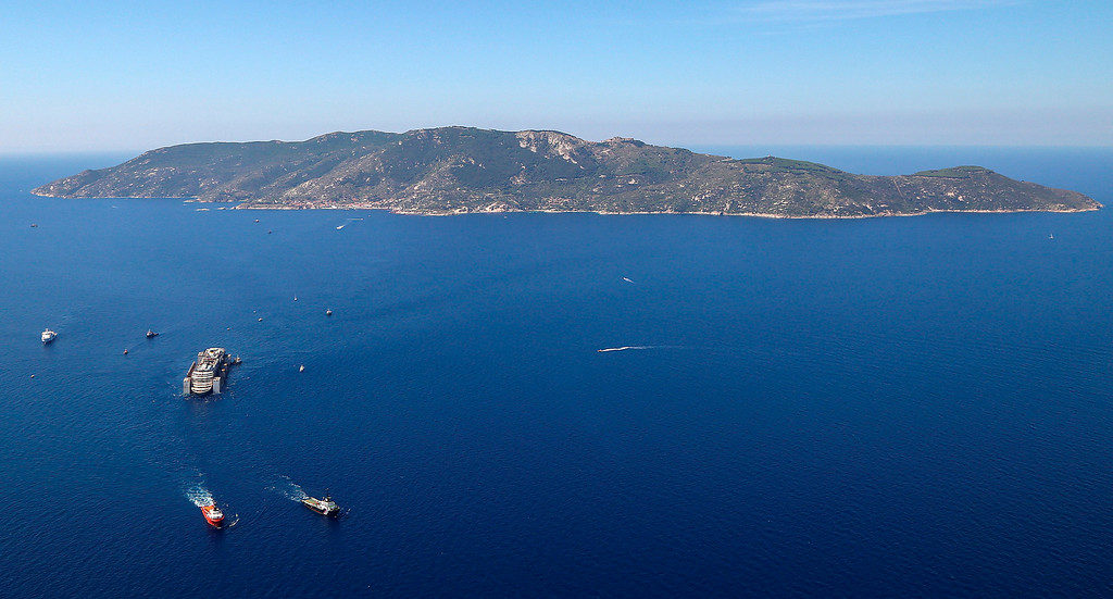 . The wreck of the Costa Concordia is towed by two tugboats as it leaves behind the tiny Tuscan island of Isola del Giglio,  Italy, Wednesday, July 23, 2014. The Costa Concordia cruise liner has begun its final voyage away from the tiny Italian island where it capsized on Jan. 13, 2012, killing 32 people. (AP Photo/Courtesy of the Italian Civil Protection Department, ho)
